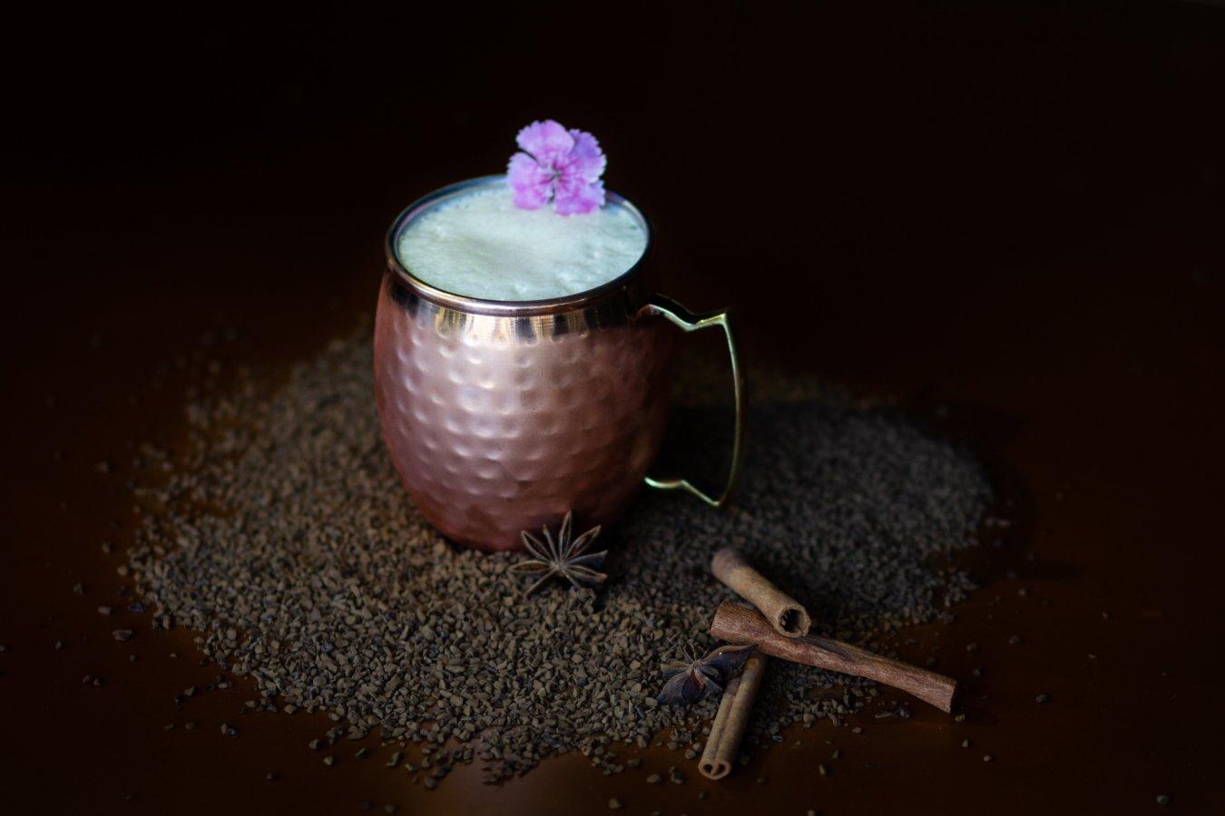 taza de café en coctel con varitas de canela y una flor morada en fondo negro