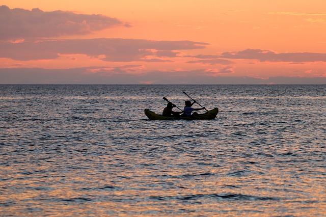 two people in a kayak paddling in the sea at sunset