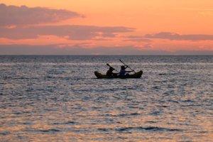 dos personas en un kayak remando en el mar al atardecer