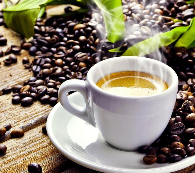 taza de café con granos al rededor sobre una mesa de madera