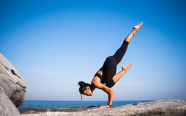 woman performing a yoga pose in front of the sea on a rock and background sky